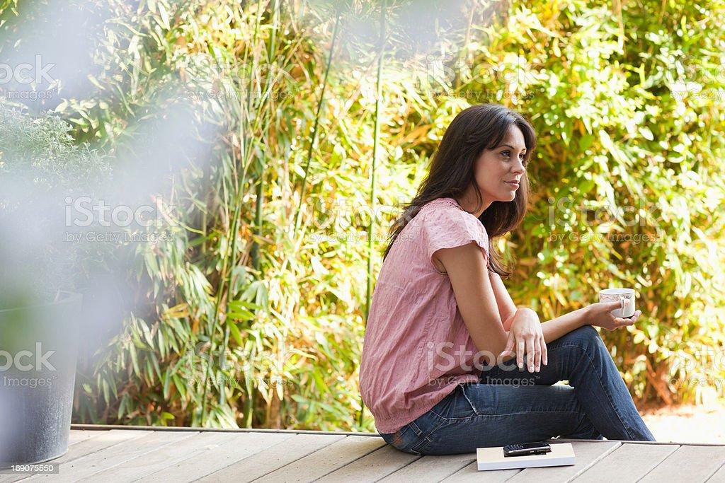 Woman drinking coffee on patio royalty-free stock photo