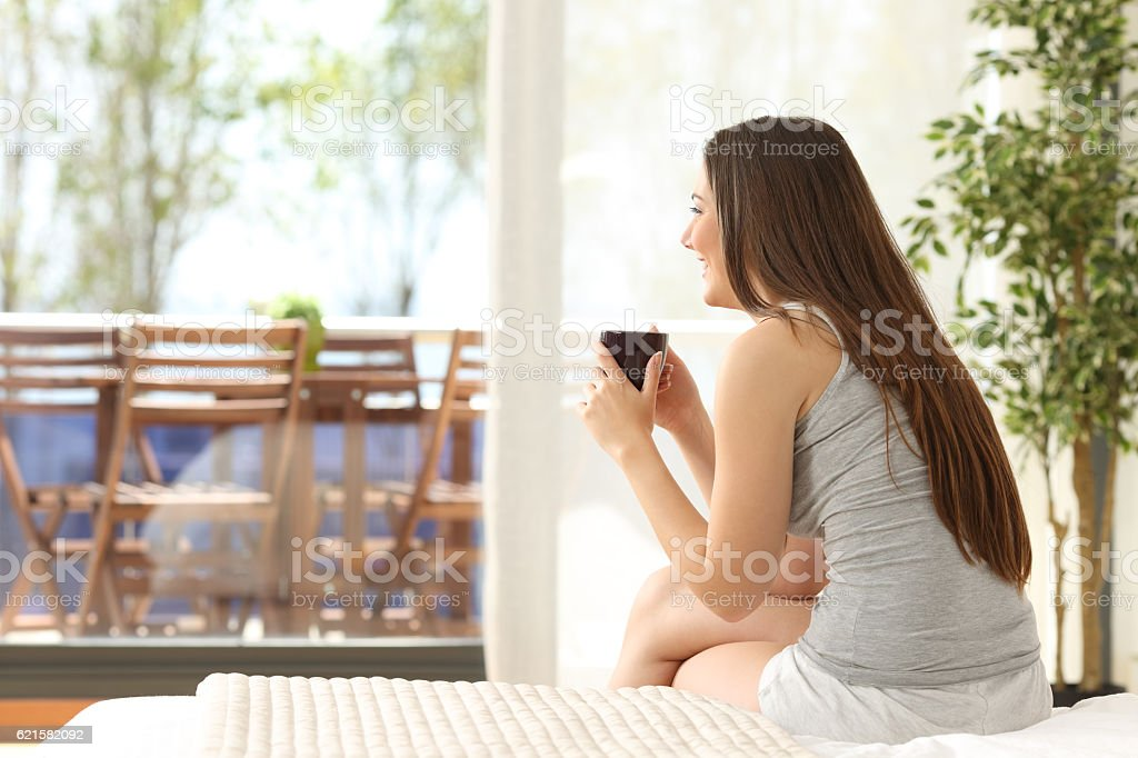 Woman drinking coffee on the bed stock photo