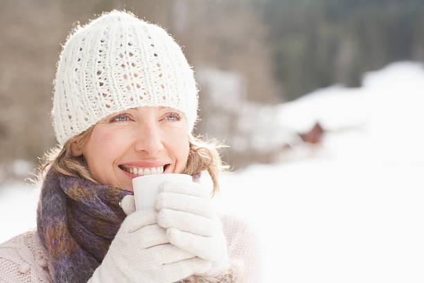 frau trinkt kaffee im schnee - kalte sonne stock-fotos und bilder