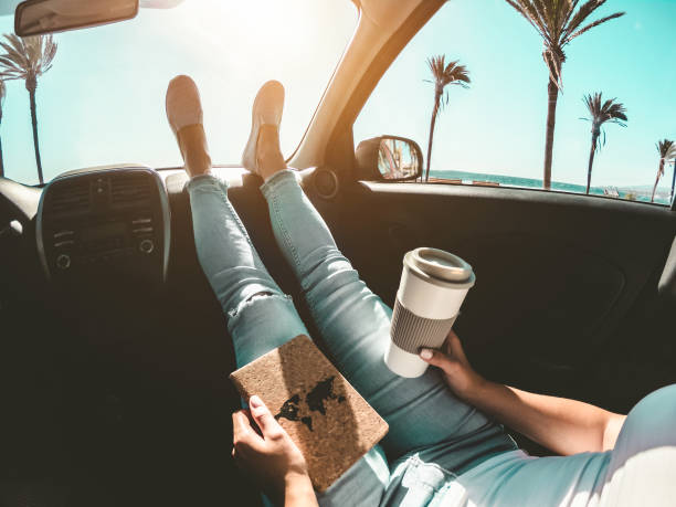 woman drinking coffee paper cup inside car with feet on dashboard - girl relaxing in auto trip reading travel book with ocean beach and palms in background - traveler concept - focus on hands - car chill foto e immagini stock