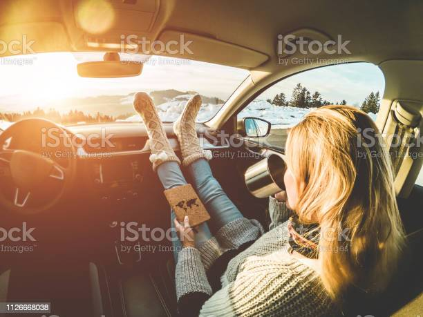 Photo of Woman drinking coffee paper cup inside car with feet warm socks on dashboard - Girl relaxing in auto trip reading travel book with snow mountains in background - Traveler concept - Focus on feet
