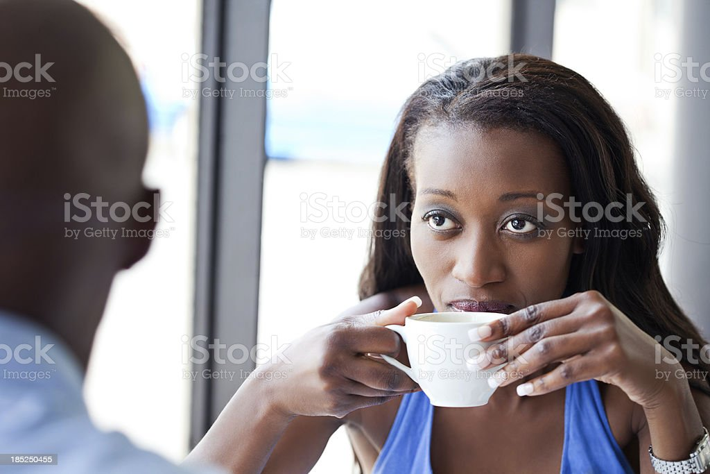 Woman drinking coffee Focus on the beautiful african woman enjoying coffee with her partner. Adult Stock Photo