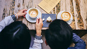 A close up of a coffee with latte art on a wooden table being lifted and enjoyed by a young woman.