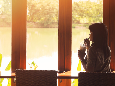 woman drinking cold coffee and sitting at coffee shop