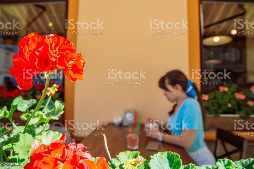 woman drinking cool drinks in cafe. focus on flower in front. blurred background stock photo