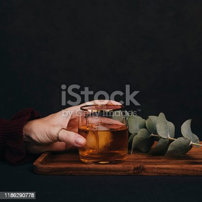 Woman drinking drink brandy whiskey or rum on ice Close up of hands and glass of alcohol