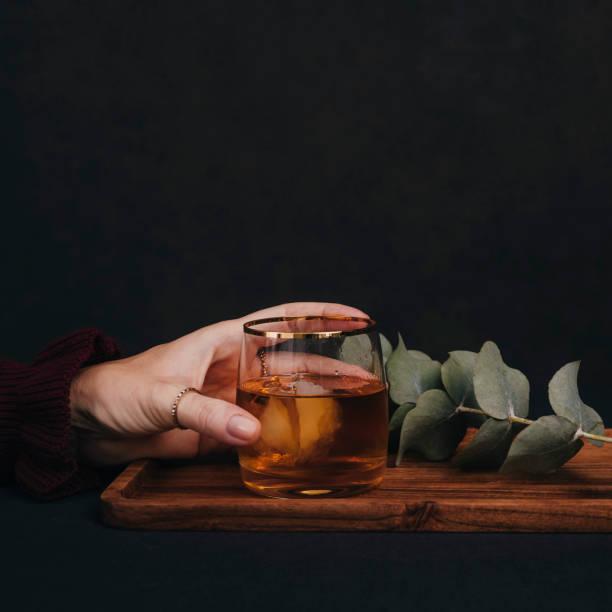 Mujer bebiendo whisky de brandy o ron sobre hielo - foto de stock