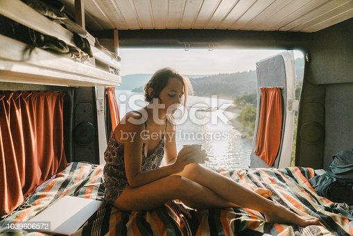 Young Caucasian woman drinking from cap in campervan near Lake of Sainte-Croix