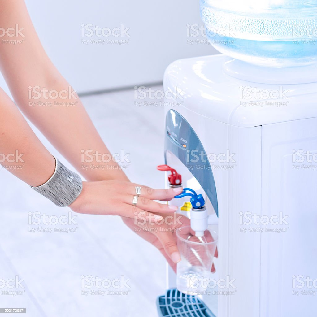Woman Drinking from Water Cooler stock photo