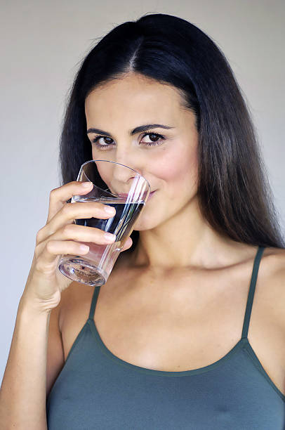 woman drinking glass of water stock photo