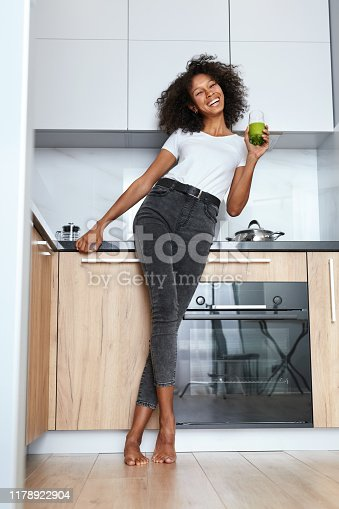 Woman drinking green detox juice, smoothie drink in kitchen. Happy smiling african girl with glass of healthy fresh raw vegetable smoothie at home. Diet nutrition concept