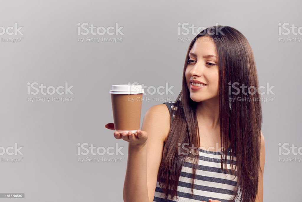 Woman drinking hot drink from disposable paper cup stock photo