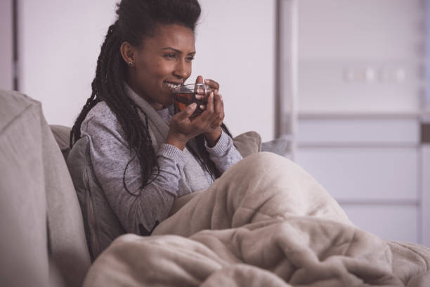 Woman drinking hot tea, comfortable sitting on a couch. stock photo