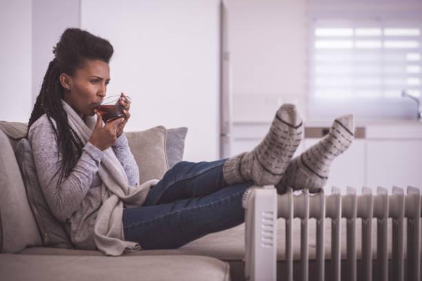 Woman drinking hot tea, heating feet at home. stock photo