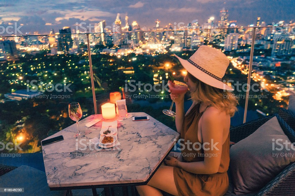 Woman drinking in rooftop bar in Bangkok圖像檔