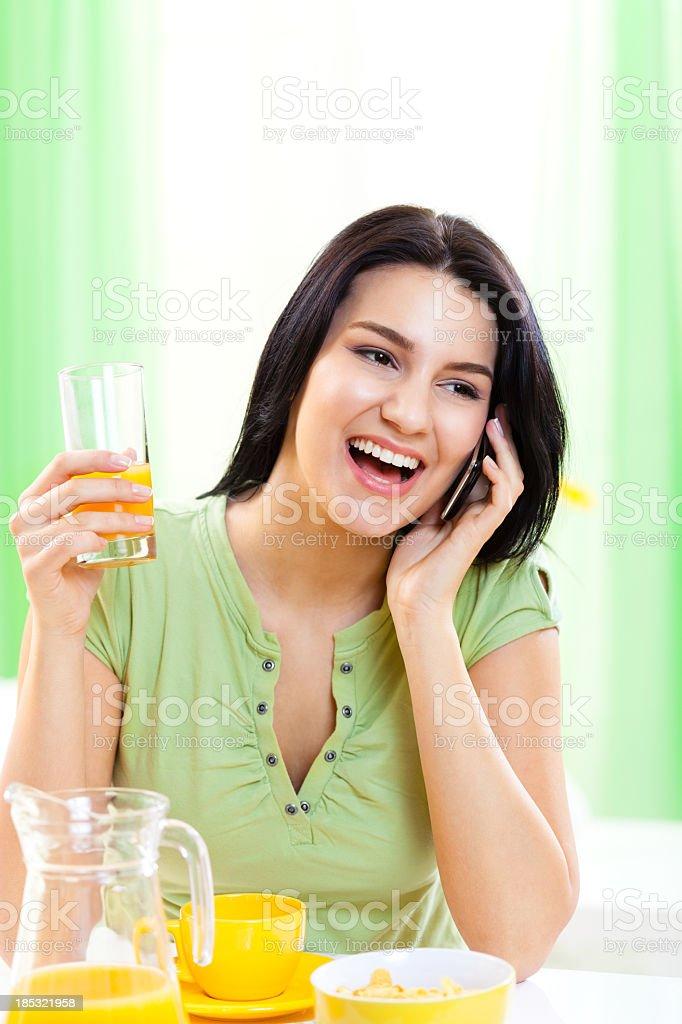 Woman drinking orange juice, talking on mobile phone royalty-free stock photo
