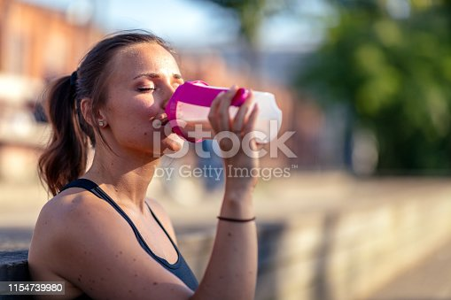 A young woman is sitting outdoors in work out clothes. She is holding a protein shake.