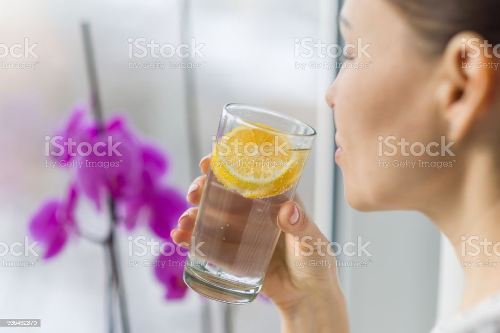Woman drinking summer refreshing fruit flavored infused water with fresh organic lemon.