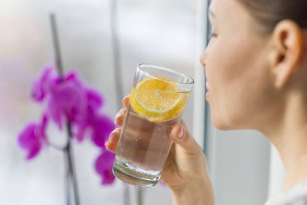 woman drinking summer refreshing fruit flavored infused water with fresh organic lemon. - limone foto e immagini stock