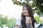 公園でタピオカを飲む女性