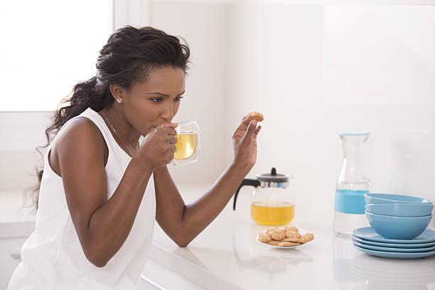woman drinking tea and eating cookies in the morning. - grüner tee koffein stock-fotos und bilder