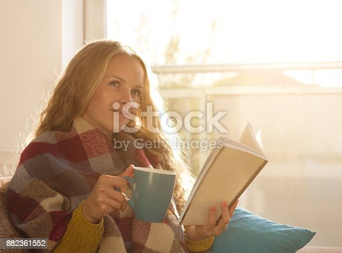 istock Woman drinking tea and reading book 882361552