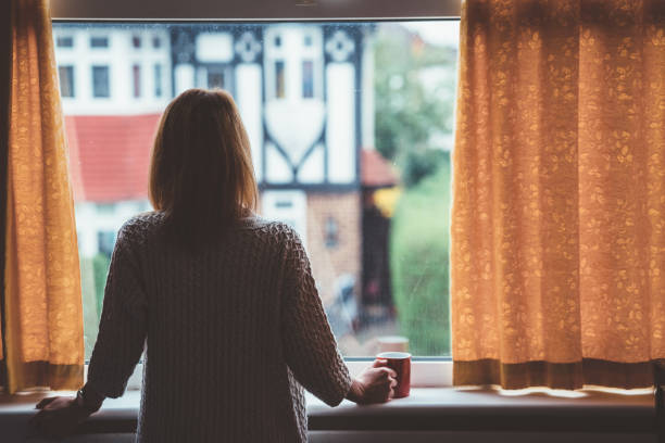 Woman drinking tea at home Rear view of woman at home staring through the window desolation stock pictures, royalty-free photos & images