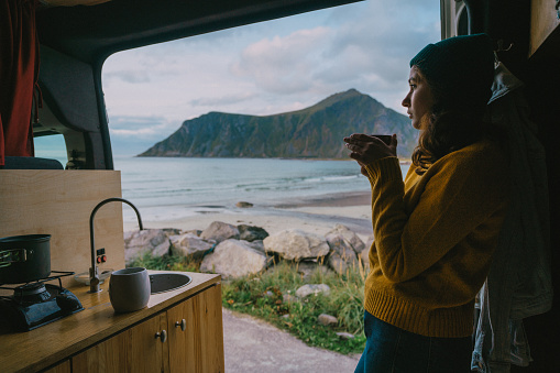 Young Caucasian woman drinking tea in camper van with view on beach on Lofoten Island