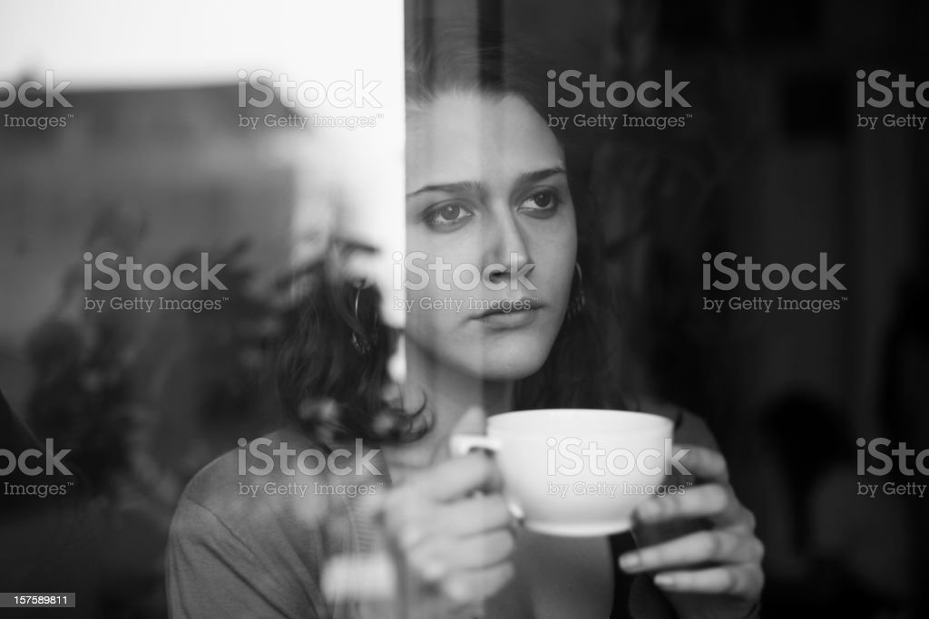 Woman drinking tea looking outside the window royalty-free stock photo