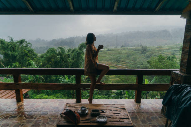 Woman drinking tea on balcony with view  on rice fields stock photo