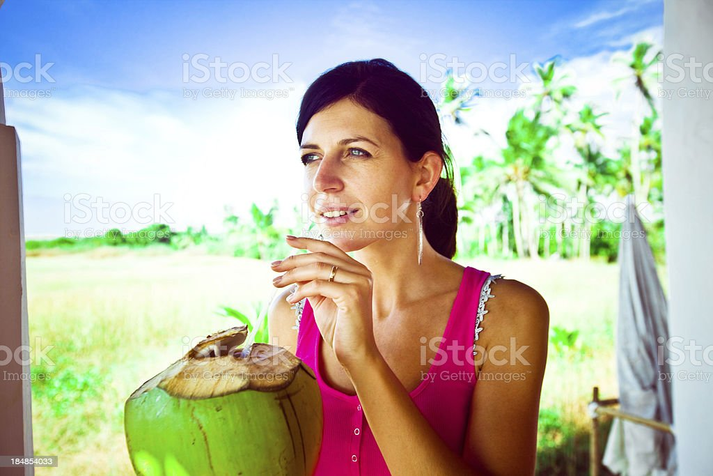 Woman drinking tropical cocktail Pretty woman drinking coconut water drink on the tropical vacation, coconut palm grove in the background. 30-34 Years Stock Photo