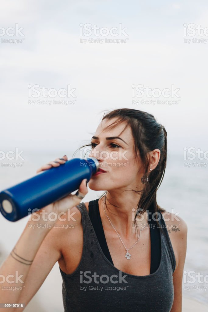 Woman drinking water after a workout stock photo