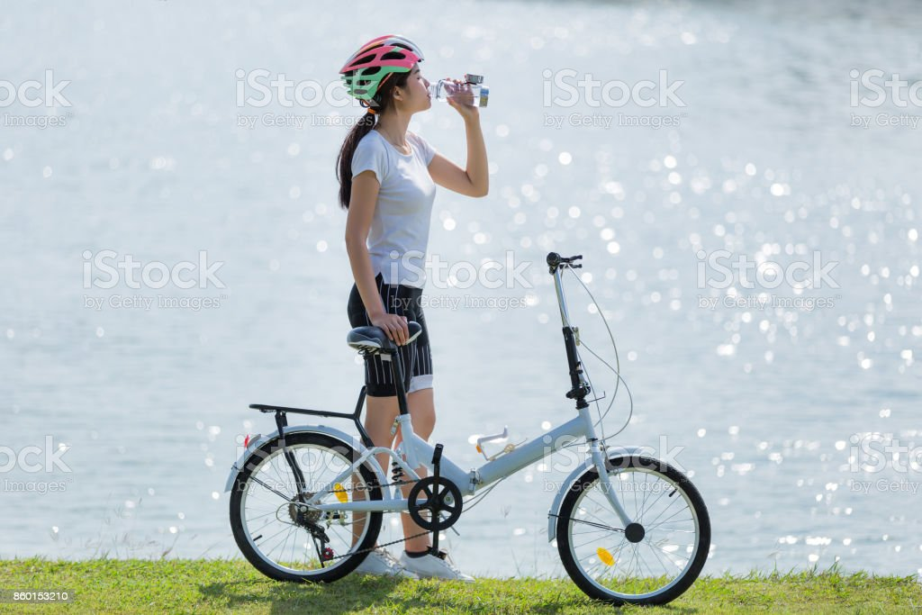 Woman drinking water after exercise bike. stock photo