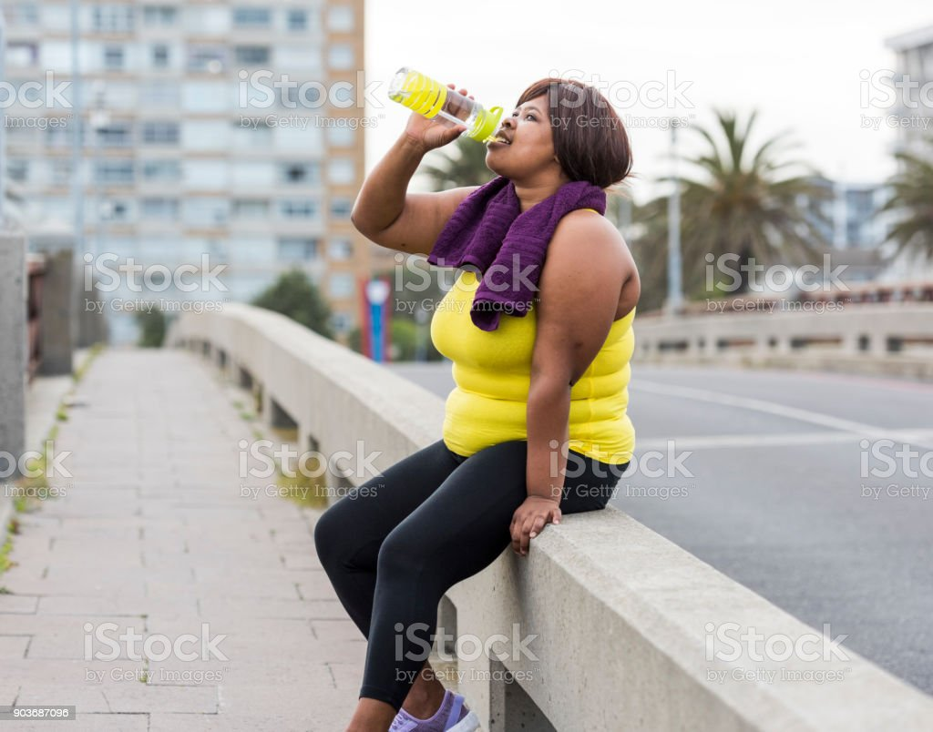 Woman drinking water after exercise stock photo