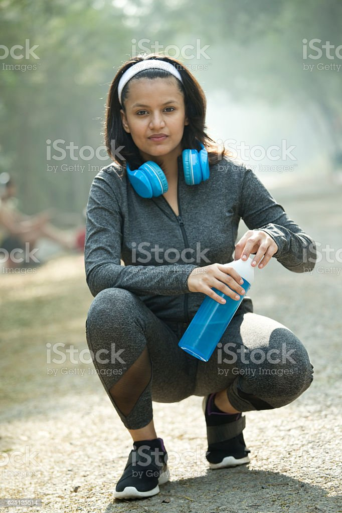 Woman drinking water after jogging stock photo