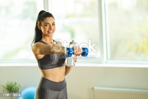 1035512048istockphoto Woman drinking water and exercising at home 1195776378