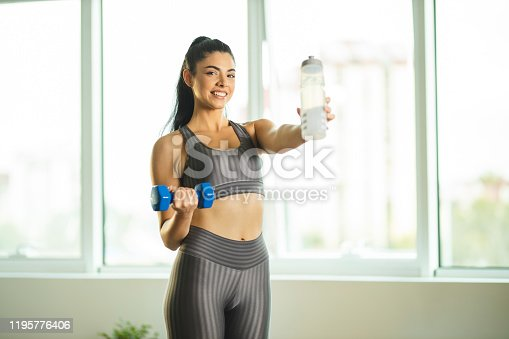 1035512048istockphoto Woman drinking water and exercising with dumbbells 1195776406