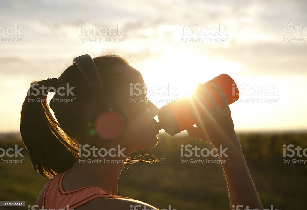 Woman drinking water at sunset royalty-free stock photo