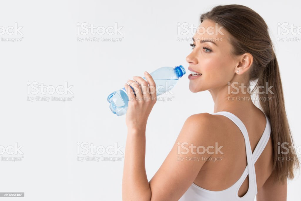 Woman drinking water from blue bottle stock photo