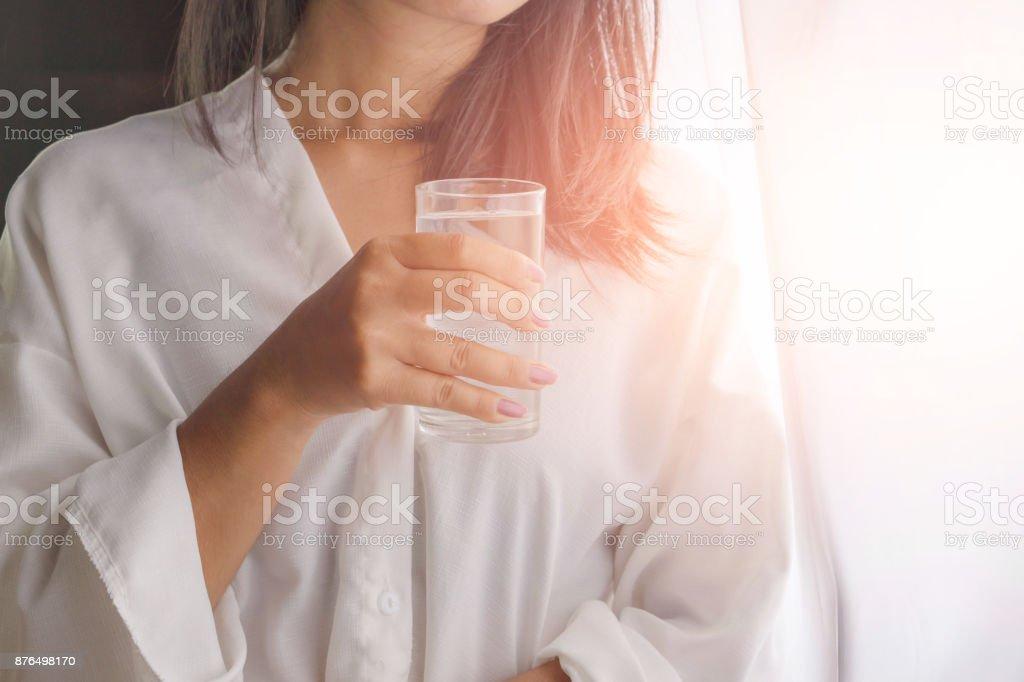 Frau Trinkwasser aus Glas neben dem Fenster – Foto