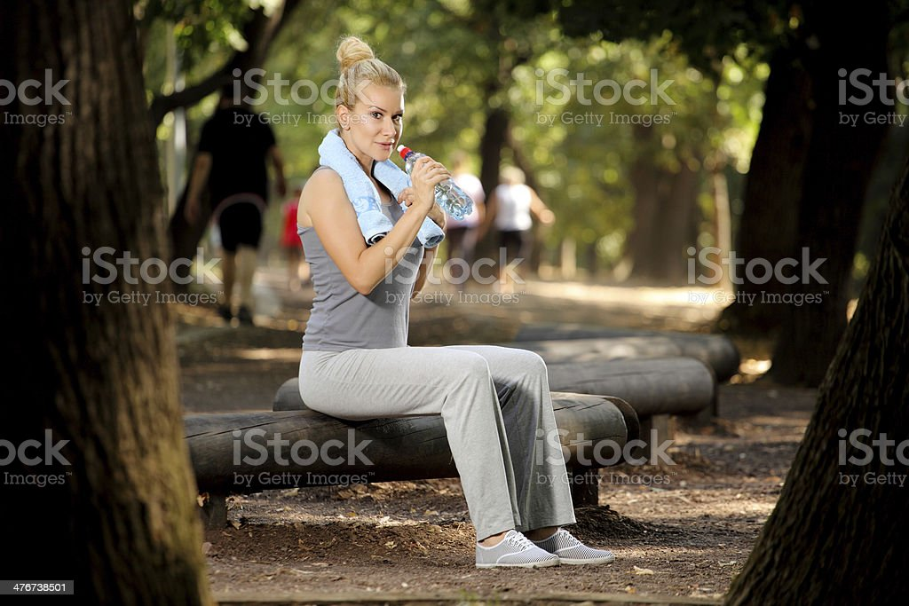 Woman drinking water in park royalty-free stock photo