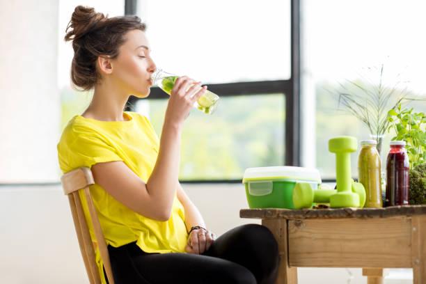 frau trinkwasser im haus - wasser trinken abnehmen stock-fotos und bilder