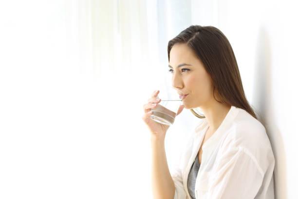 frau trinkwasser seitlich isoliert - wasser trinken abnehmen stock-fotos und bilder