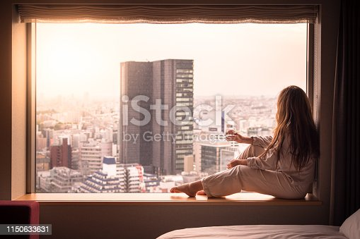 A woman is relaxed in her pajamas, and looking out of her hotel window while she sips on a glass of water. She's looking at the cityscape of Shibuya, Tokyo, Japan below. Shot in the morning in Spring.
