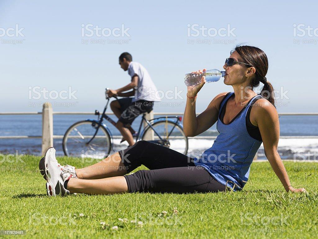 Woman Drinking Water On Grass Near Sea stock photo