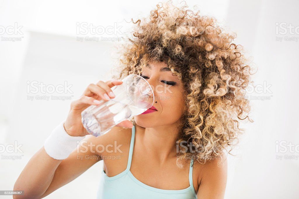 Woman drinking water. Young African American woman drinking water after exercising. Drinking Water Stock Photo