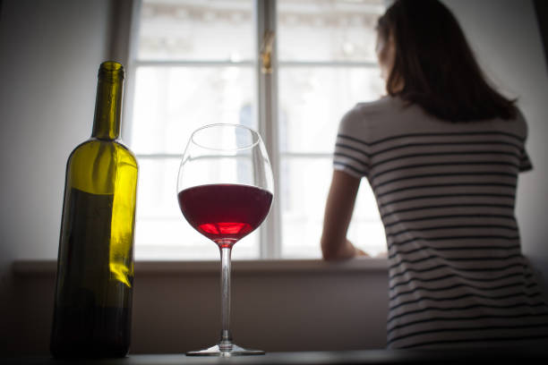 Woman drinking wine alone in the dark room - foto stock