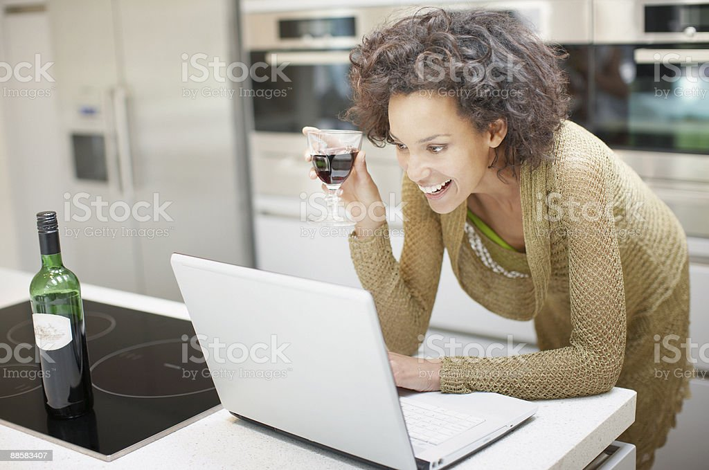 Woman drinking wine and using laptop at home royalty-free stock photo