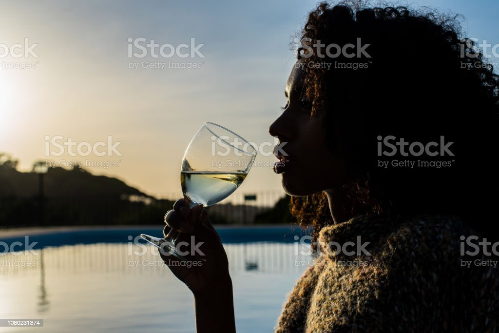 Woman drinking wine by the swimming pool stock photo