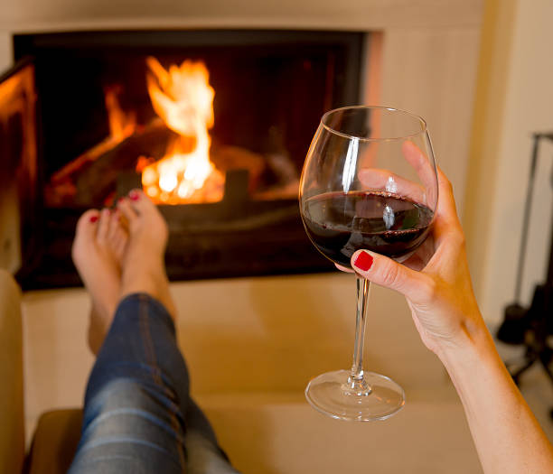 woman drinking wine in front of fire Woman holding a glass of red wine sitting in front of an open fire log fire stock pictures, royalty-free photos & images